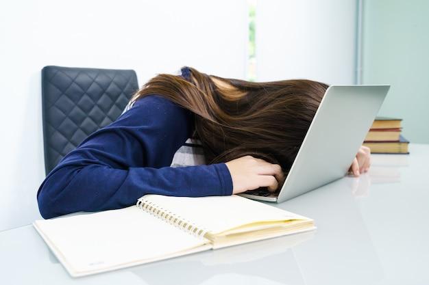 I capelli lunghi della giovane donna si addormentano sullo scrittorio con il computer portatile