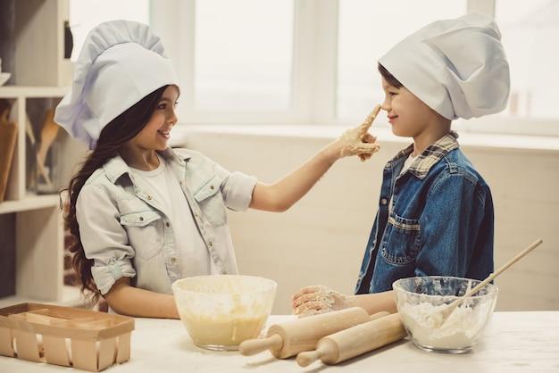 I cappelli da cuoco sorridono mentre cuociono in cucina.