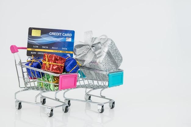 I carrelli della spesa e la carta di credito con le scatole regalo completamente montate su carrelli, acquisti online e-commerce.