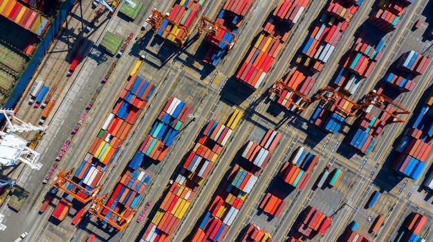 I carrelli elevatori retrattili con vista aerea spostano i container in un terminal merci