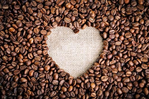 I chicchi di caffè fritti si trovano sotto forma di cuore sui bordi di legno e sulla tela da imballaggio.