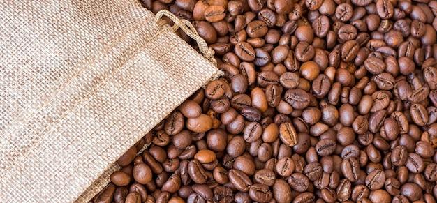 I chicchi di caffè fuoriescono dal sacchetto. sullo sfondo di chicchi di caffè.