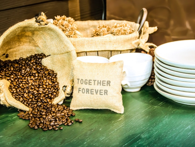 I chicchi di caffè in un sacco sono posti su un tavolo di legno verde con una tazza di caffè e un piattino bianco.
