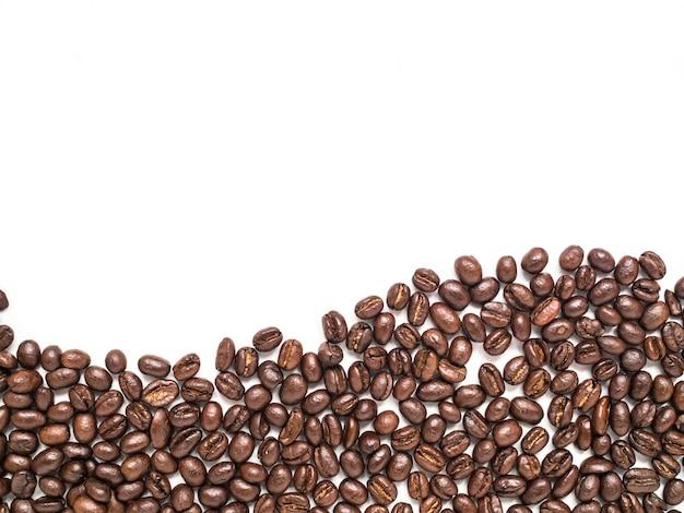 I chicchi di caffè isolati sistemano nella parte inferiore nella forma della linea della curva per fondo