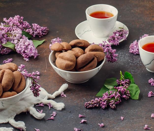 I chicchi di caffè modellano i biscotti con le tazze bianche di tè.