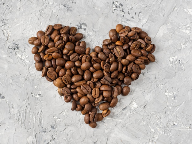 I chicchi di caffè sono sul tavolo a forma di cuore