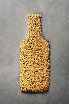I chicchi di malto sono disposti come una bottiglia di birra su uno sfondo grigio di cemento.