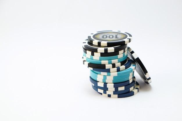 I chip di poker o del casinò si accumulano nel fondo bianco isolato