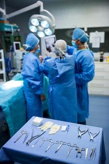 I chirurghi che parlano sulla radiografia del paziente in sala operatoria