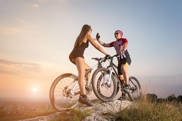I ciclisti di coppia si danno il cinque l'un l'altro sullo sfondo di un magnifico tramonto