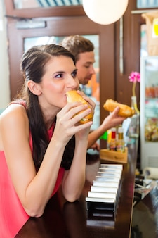 I clienti che mangiano hot dog in snack bar fast food