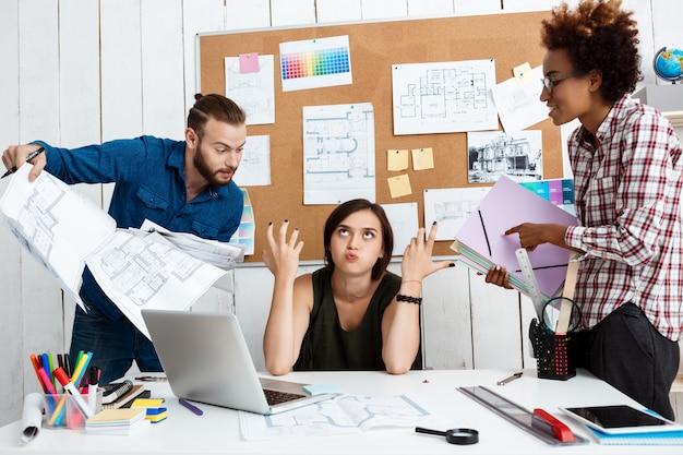 I colleghi discutono, discutono di disegni, nuove idee in ufficio