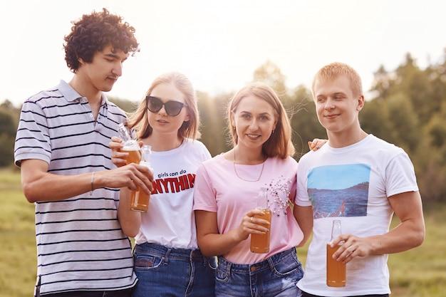 I compagni di gruppo si incontrano per un picnic, celebrano l'anno di studio finito con successo, tengono bottiglie di birra o energy drink, si trovano uno accanto all'altro