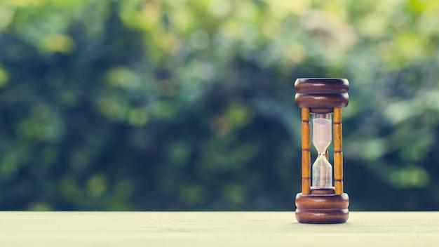 I concetti del tempo. clessidra sulla tavola di legno con la natura verde