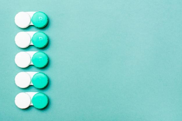 I contenitori di lenti si trovano in fila ordinata su uno sfondo verde. .