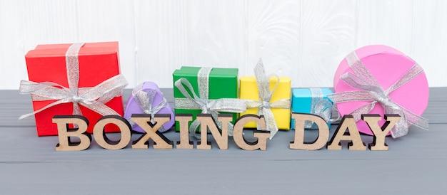 I contenitori di regalo sono legati con un nastro con le parole giorno di pugilato su fondo bianco di legno