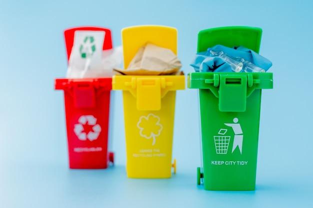 I contenitori di riciclaggio gialli, verdi e rossi con riciclano il simbolo su fondo blu. mantieni la città in ordine, lascia il simbolo del riciclaggio. concetto di protezione della natura