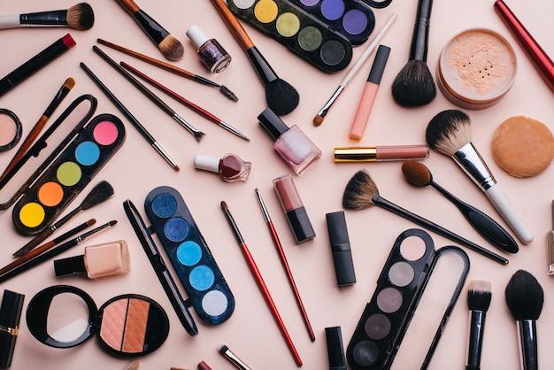 I cosmetici e il trucco delle donne hanno messo su fondo rosa. vista dall'alto