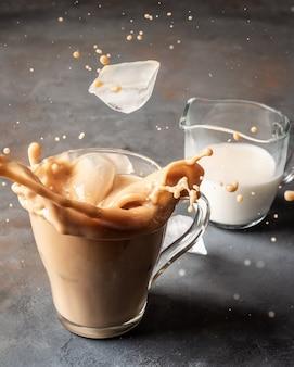 I cubetti di ghiaccio cadono in un bicchiere con caffè e latte sollevando uno spray.