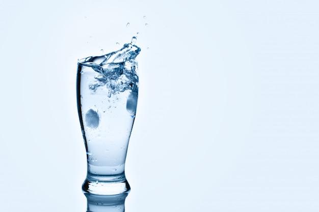 I cubetti di ghiaccio che lambiscono il bicchiere d'acqua. spruzzi d'acqua,