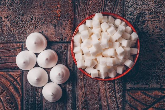 I cubi dello zucchero bianco in una ciotola con il piano delle caramelle giacciono su una tavola di legno scura