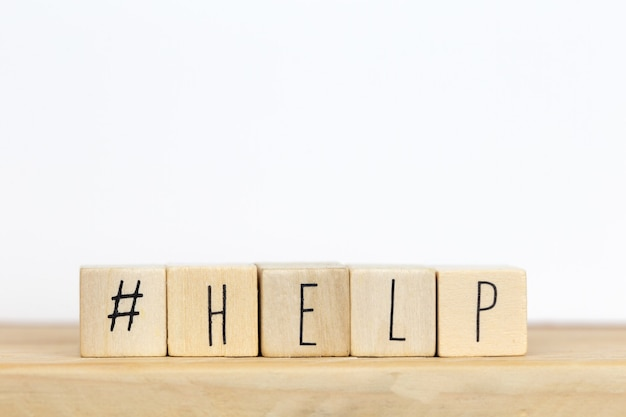I cubi di legno con un hashtag e la parola aiutano, concetto sociale di media