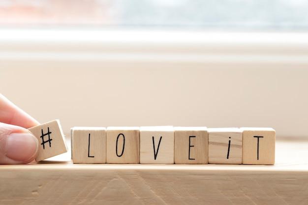 I cubi di legno con un hashtag e le parole lo adorano, fondo di concetto di media sociali