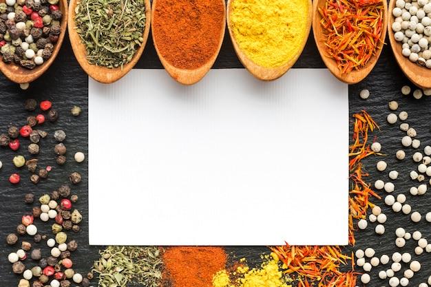 I cucchiai del primo piano con polvere di spezie e condimenti si diffondono sul tavolo
