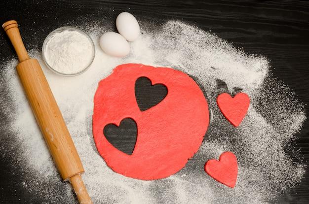 I cuori rossi hanno tagliato la pasta con il mattarello, le uova e la farina su una tavola nera. vista dall'alto. copyspace