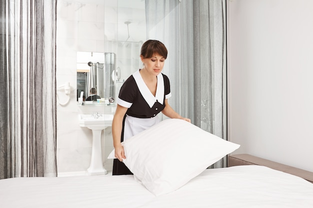 I cuscini dovrebbero essere bianchi come la neve. bella donna vicino in uniforme da cameriera che fa il letto, lavora come domestica in hotel o in casa dei proprietari, concentrandosi sui suoi doveri mentre pulisce la camera da letto