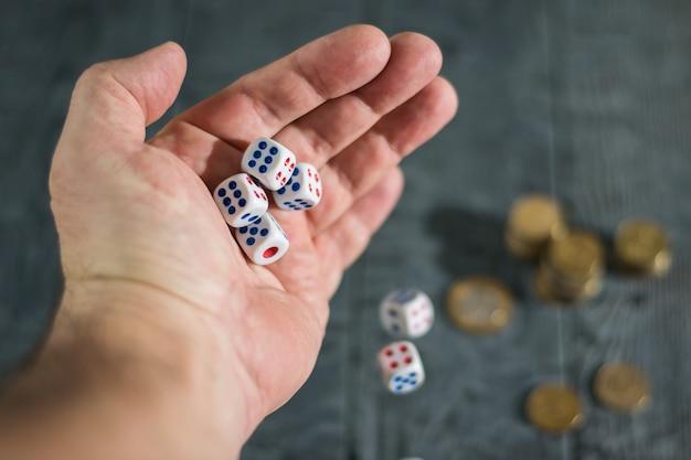 I dadi cadono dalla mano di un uomo su un tavolo di legno nero con monete d'oro