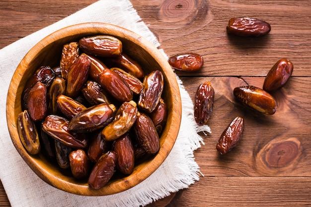 I datteri secchi dolci fruttificano in una ciotola di legno e sulla tavola. vista dall'alto
