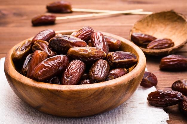 I datteri secchi dolci fruttificano in una ciotola di legno sulla tavola