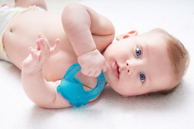 I denti del bambino vengono tagliati. ragazzo carino con occhi blu sgranocchia un giocattolo.