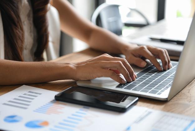 I dirigenti di sesso femminile utilizzano laptop sulla scrivania in ufficio.