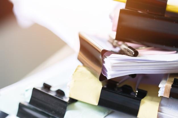 I documenti incompleti impilano i file di carta sulla scrivania per pile di documenti di rapporto non finiti