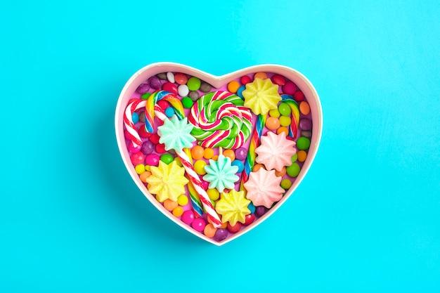 I dolci al cioccolato mix si trovano a forma di scatola regalo di cuore su sfondo colorato