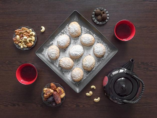 I dolci fatti a mano del ramadan sono serviti con tè sul tavolo di legno scuro. biscotti egiziani