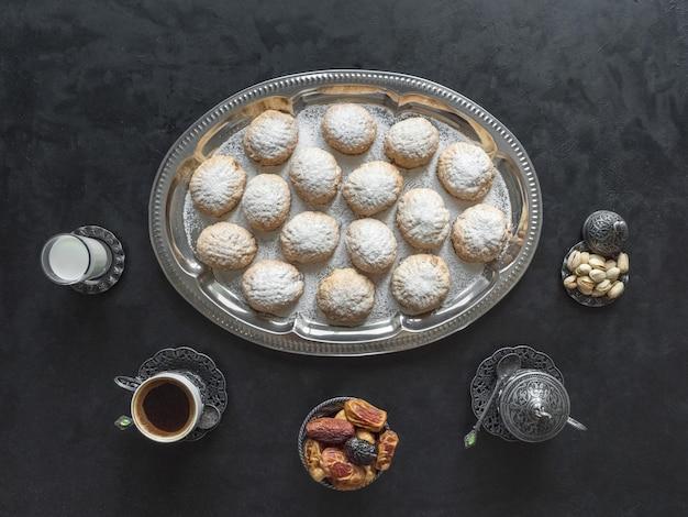 I dolci festivi del ramadan sono serviti con tè sul tavolo nero. biscotti egiziani