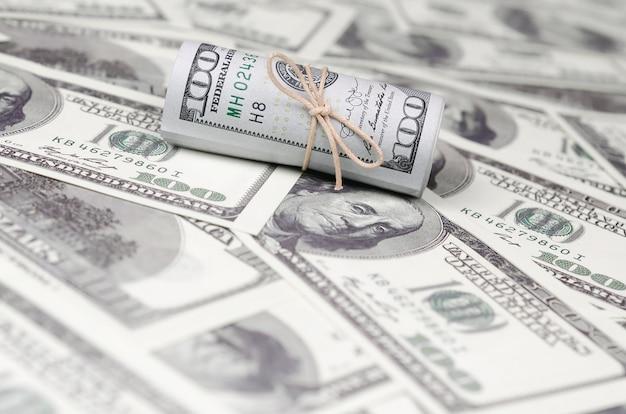 I dollari americani arrotolati e stretti con la banda giacciono su molte banconote americane