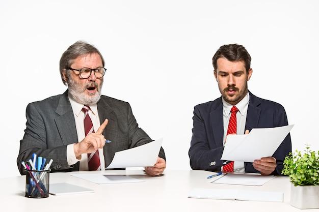 I due colleghi che lavorano insieme in ufficio su sfondo bianco. discutono attivamente ed emotivamente i piani attuali