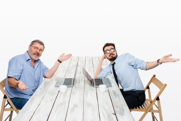 I due colleghi che lavorano insieme in ufficio su sfondo bianco. si siedono al tavolo con i computer ed entrambi si stringono nelle spalle come a dire -è successo