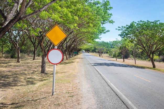 I due lati della strada di campagna con alberi e un segno bianco (per testo e simbolo di input)