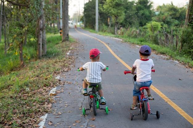 I due ragazzi adorabili stanno andando in bici in bici.