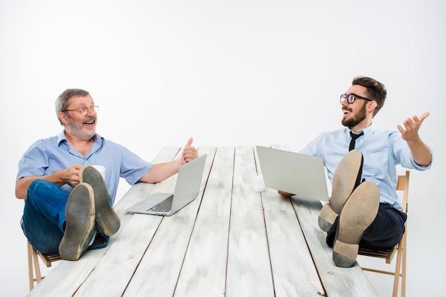 I due uomini d'affari sorridenti con le gambe sul tavolo che lavorano su laptop su sfondo bianco. affari in stile americano