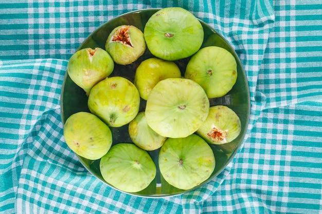 I fichi verdi in un piatto piatto giacevano su un panno da picnic