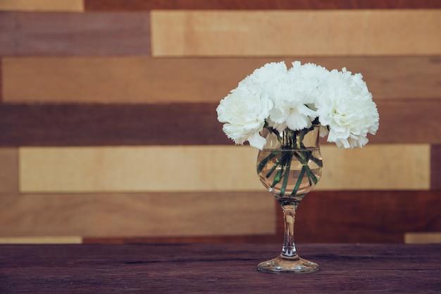 I fiori bianchi sono disposti in un bicchiere d'acqua posizionato su fondo in legno.