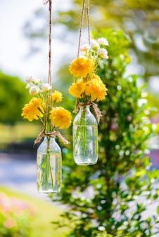 I fiori di calendula in una bottiglia di vetro appeso