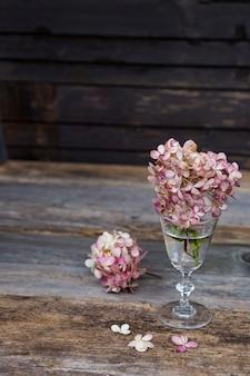 I fiori di un'ortensia rosa stanno su una tavola di legno in un vecchio vetro trasparente