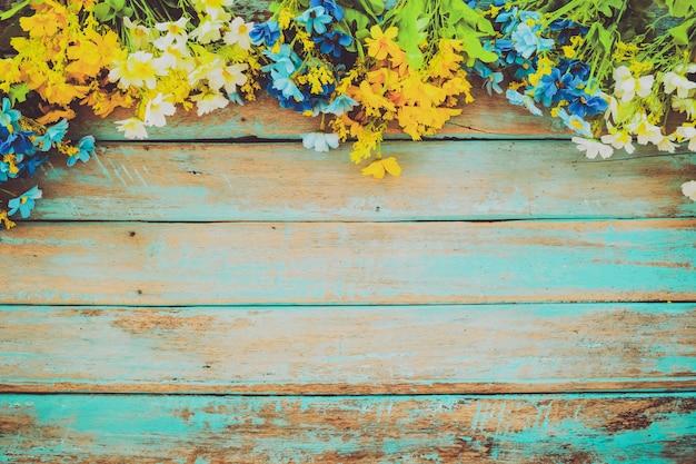 I fiori sbocciano su fondo di legno d'annata, progettazione della struttura del confine